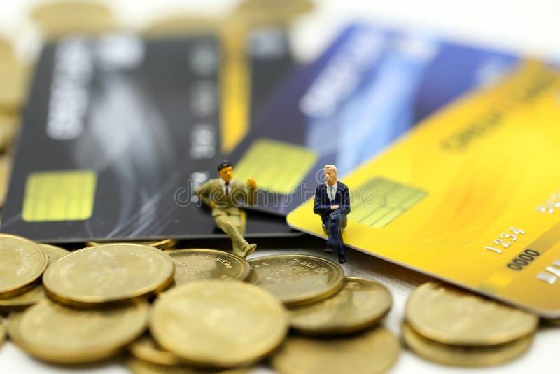 Μικροσκοπικοί άνθρωποι: επιχειρηματίας με τα νομίσματα πιστωτικών καρτών και σωρών, την υποχρέωση, τη συμφωνία, την επένδυση, την στοκ φωτογραφία