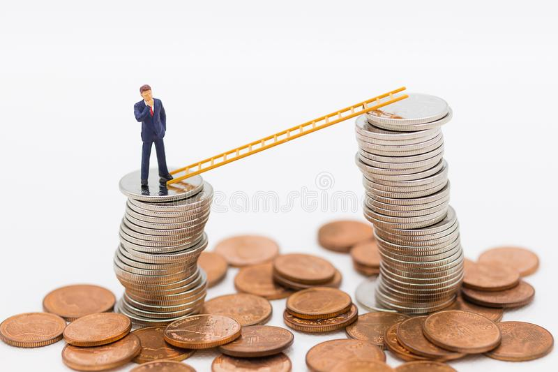Μικροσκοπικοί άνθρωποι: Επιχειρηματίας που σκέφτεται και που στέκεται στο σωρό των νομισμάτων με το σκαλοπάτι που καταναλώνει ως  στοκ εικόνες