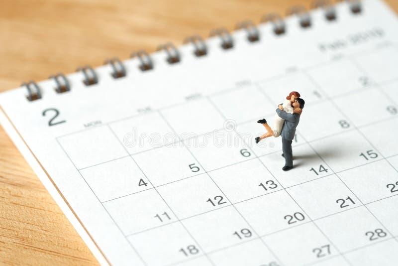 Μικροσκοπικοί 2 άνθρωποι ζεύγους που στέκονται στο ημερολόγιο Η ημέρα 14 συναντά Val στοκ φωτογραφία