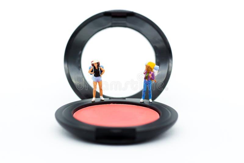 Μικροσκοπικοί άνθρωποι: Οι γυναίκες στέκονται σε μια βούρτσα στο μάγουλο για το makeup Im στοκ εικόνες