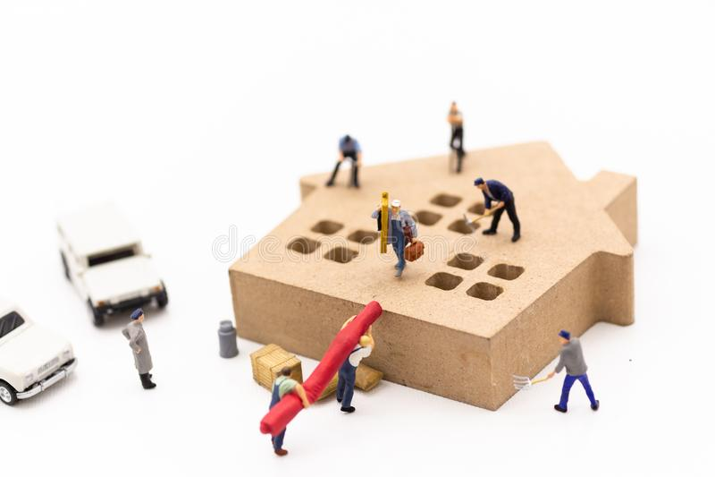 Μικροσκοπικοί άνθρωποι: Οι εργαζόμενοι βοηθούν να χτίσουν ένα σπίτι Εικόνα εμείς στοκ φωτογραφίες