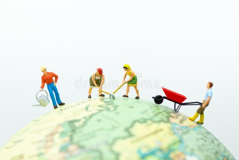 Μικροσκοπικοί άνθρωποι: Οι χωρικοί καλλιεργούν στη σφαίρα Χρήση εικόνας για βιομηχανικός και γεωργικός στοκ εικόνα
