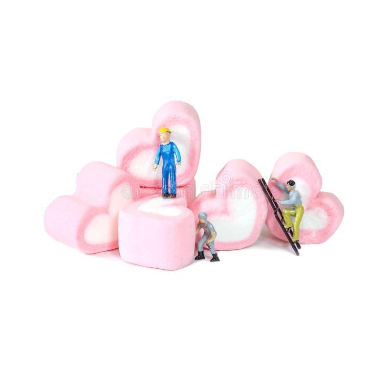 Μικροσκοπικοί άνθρωποι που εργάζονται με τις γλυκές marshmallow καραμέλες, στοκ φωτογραφία
