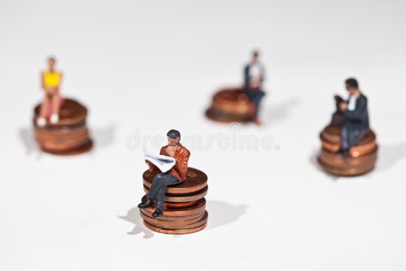 Μικροσκοπικοί άνθρωποι που κάθονται στα νομίσματα στοκ φωτογραφία