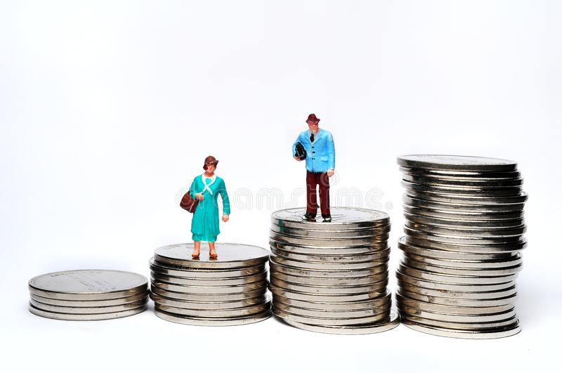 Μικροσκοπικοί άνθρωποι που στέκονται στο σωρό των νομισμάτων με το διαφορετικό ύψος στοκ φωτογραφίες με δικαίωμα ελεύθερης χρήσης