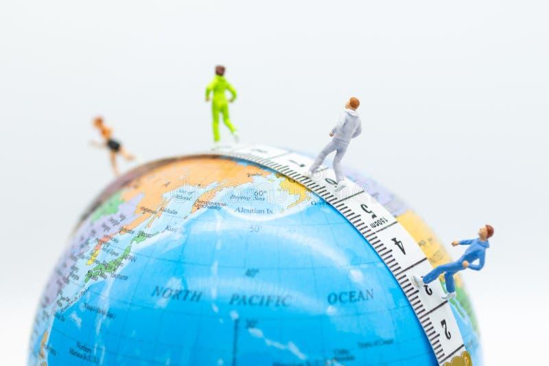 Μικροσκοπικοί άνθρωποι που τρέχουν στο waistline με τον παγκόσμιο χάρτη Χρήση εικόνας για την υγιή, έννοια άσκησης στοκ εικόνα με δικαίωμα ελεύθερης χρήσης