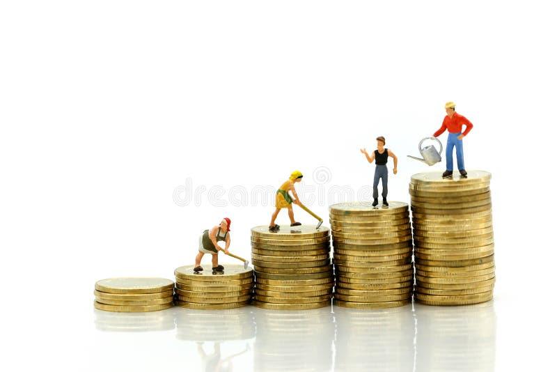Μικροσκοπικοί άνθρωποι: στάση αγροτών πάνω από τα νομίσματα, χρήματα, Financi στοκ εικόνες