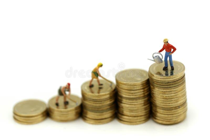 Μικροσκοπικοί άνθρωποι: στάση αγροτών πάνω από τα νομίσματα, χρήματα, Financi στοκ εικόνα