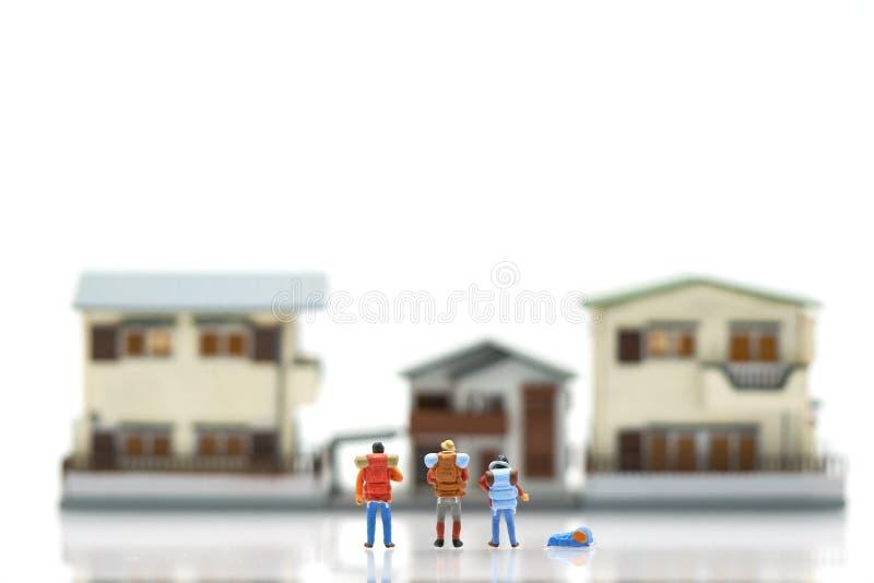 Μικροσκοπικοί 3 άνθρωποι στέκονται στα πρότυπα σπιτιών και ξενοδοχείων να επιλέξουν μια θέση για να ζήσουν μέσα χρησιμοποίηση ως  στοκ εικόνα