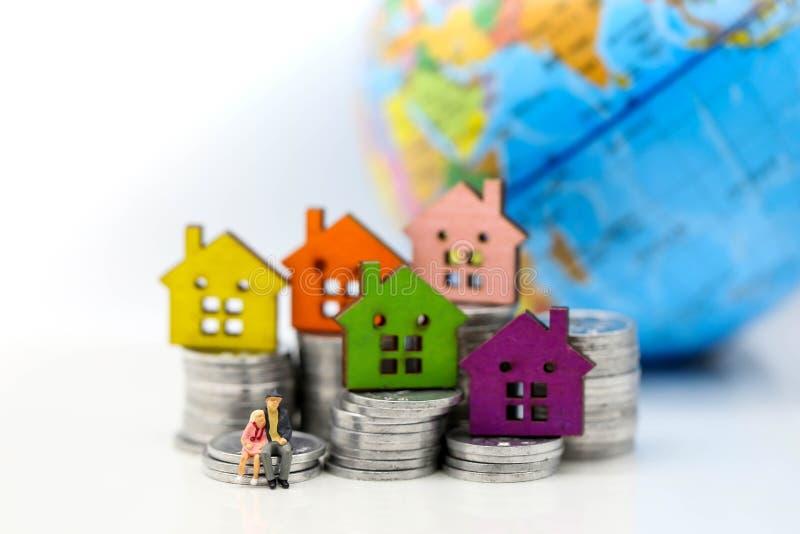 Μικροσκοπικοί άνθρωποι: στεμένος στο σωρό νομισμάτων με το σπίτι, savi χρημάτων στοκ φωτογραφία με δικαίωμα ελεύθερης χρήσης