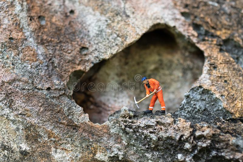 Μικροσκοπικοί άνθρωποι: Τα άτομα σε ομοιόμορφο χρησιμοποιούν τα φτυάρια για να τρυπήσουν τις πέτρες με τρυπάνι Χρήση εικόνας για  στοκ φωτογραφία