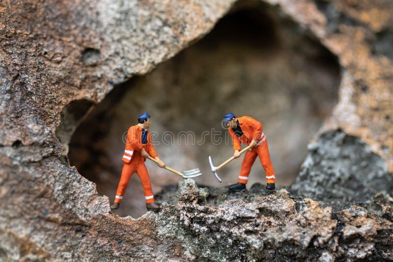 Μικροσκοπικοί άνθρωποι: Τα άτομα σε ομοιόμορφο χρησιμοποιούν τα φτυάρια για να τρυπήσουν τις πέτρες με τρυπάνι Χρήση εικόνας για  στοκ εικόνες