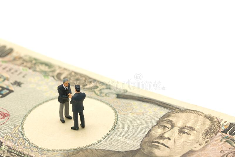 Μικροσκοπικοί 2 επιχειρηματίες ανθρώπων τινάζουν τη στάση χεριών στα ιαπωνικά τραπεζογραμμάτια αξίας 10.000 γεν χρησιμοποιώντας ω στοκ φωτογραφίες
