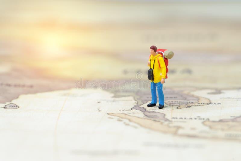 Μικροσκοπικός νεαρός άνδρας ανθρώπων backpacker που στέκεται στην εκλεκτής ποιότητας έννοια παγκόσμιας χαρτών, ταξιδιού, τουρισμο στοκ εικόνες