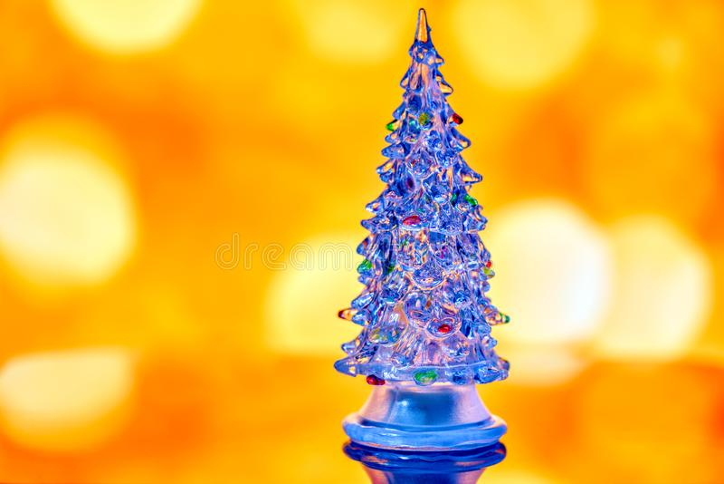 Μικροσκοπικό διαφανές χριστουγεννιάτικο δέντρο που απομονώνεται στο χρυσό λι bokeh στοκ φωτογραφίες