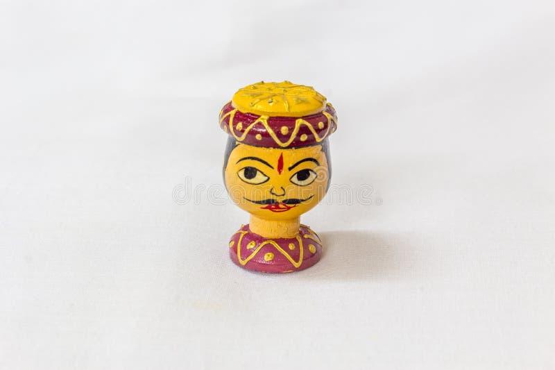 Μικροσκοπικό ζωηρόχρωμο ξύλινο παιχνίδι ενός ινδικού προσώπου ατόμων με το σχεδιασμένο βραχιόλι καπέλων και λαιμών σε ένα άσπρο υ στοκ φωτογραφίες με δικαίωμα ελεύθερης χρήσης