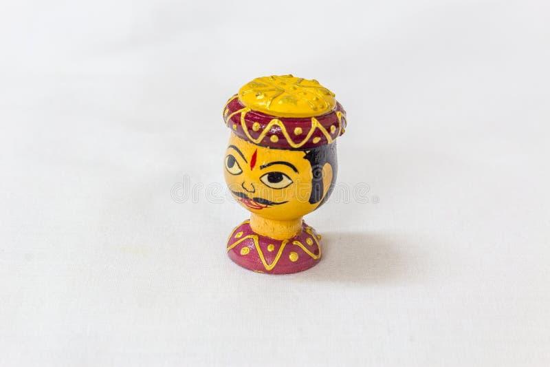 Μικροσκοπικό ζωηρόχρωμο ξύλινο παιχνίδι ενός ινδικού προσώπου ατόμων με το σχεδιασμένο βραχιόλι καπέλων και λαιμών σε ένα άσπρο υ στοκ εικόνες