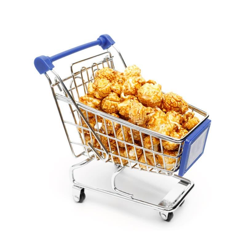 Μικροσκοπικό κάρρο αγορών μετάλλων που γεμίζουν με χρυσό γλυκό popcorn σε ένα άσπρο υπόβαθρο στοκ φωτογραφία με δικαίωμα ελεύθερης χρήσης