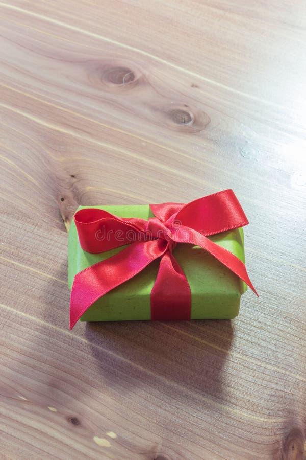 Μικροσκοπικό κιβώτιο δώρων που τυλίγεται στην Πράσινη Βίβλο με ένα μεγάλο κόκκινο τόξο σατέν, διαστημικό, ουδέτερο ξύλινο υπόβαθρ στοκ φωτογραφία με δικαίωμα ελεύθερης χρήσης