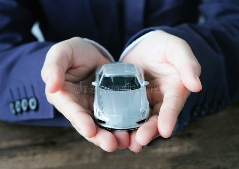 Μικροσκοπικό πρότυπο αυτοκινήτων σε διαθεσιμότητα, αυτόματος αντιπρόσωπος και έννοια ενοικίου στοκ εικόνα