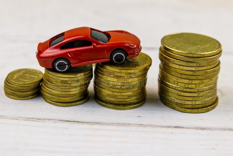 Μικροσκοπικό πρότυπο αυτοκινήτων στους σωρούς των χρυσών νομισμάτων στο άσπρο ξύλινο υπόβαθρο στοκ εικόνα