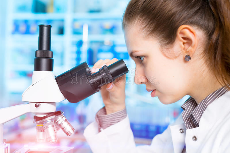 Μικροσκόπιο εργαστηριακών βοηθητικό χρήσεων γυναικών στοκ εικόνα με δικαίωμα ελεύθερης χρήσης