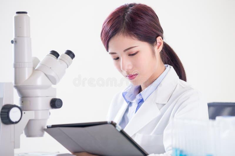 Μικροσκόπιο χρήσης επιστημόνων γυναικών στοκ φωτογραφία με δικαίωμα ελεύθερης χρήσης