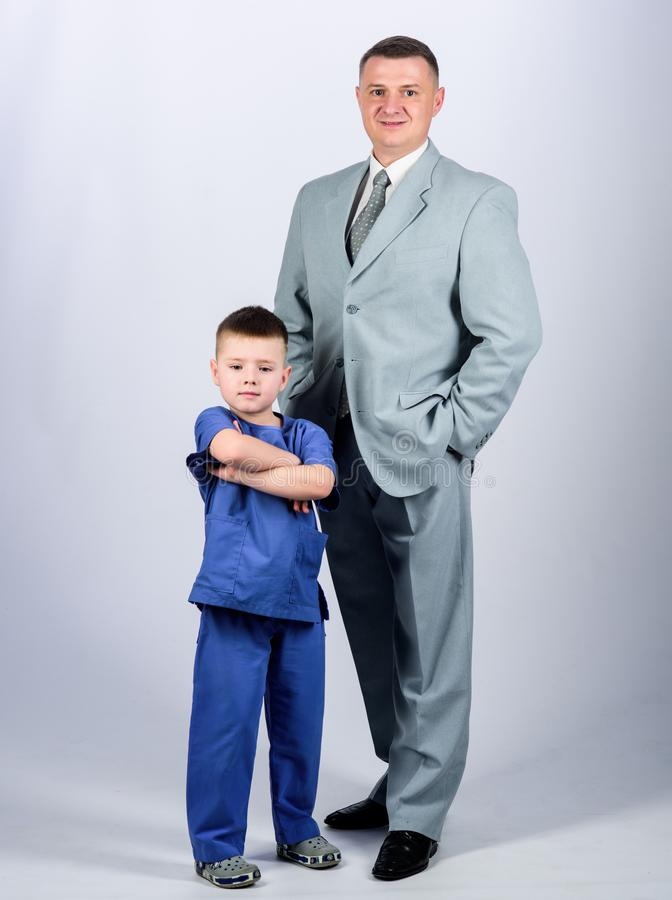Μικρός γιατρός αγοριών με τον επιχειρηματία μπαμπάδων o εμπιστοσύνη και τιμές r r πατέρας και γιος στην επιχείρηση στοκ εικόνες με δικαίωμα ελεύθερης χρήσης