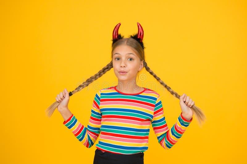 Μικρός δαίμονας μέσα Κοριτσίστικη διάθεση Χαριτωμένο αλλά επικίνδυνο Έννοια του Χάλογουιν Μικρό αξιολάτρευτο παιδί με κόκκινα κέρ στοκ εικόνες