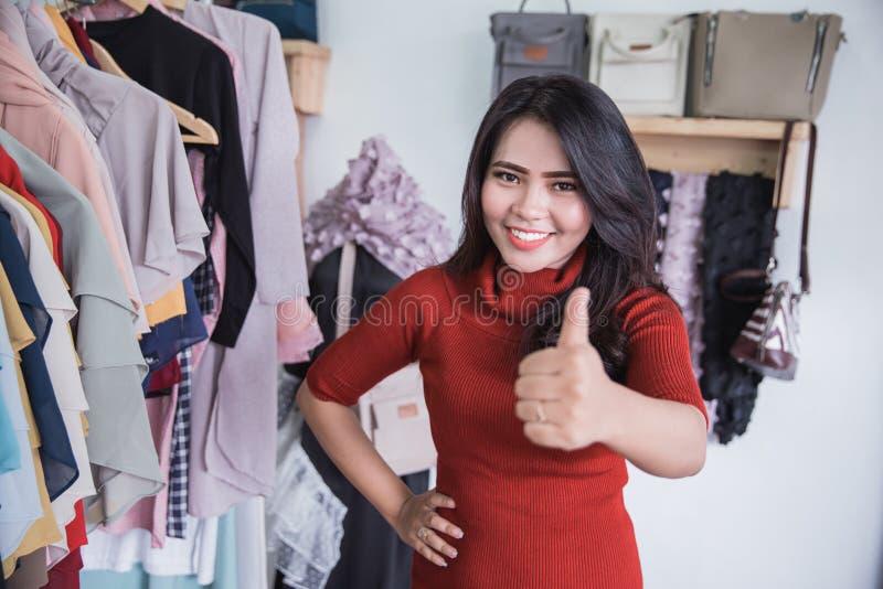 Μικρός ιδιοκτήτης καταστημάτων μόδας που παρουσιάζει αντίχειρα στοκ εικόνα με δικαίωμα ελεύθερης χρήσης