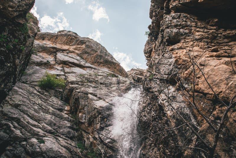 Μικρός καταρράκτης στα δύσκολα βουνά που πυροβολούνται από κάτω από στοκ εικόνες