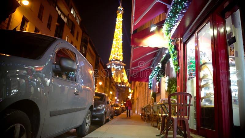 Μικρός καφές που διακοσμείται με τα φω'τα Χριστουγέννων, λαμπιρίζοντας πύργος του Άιφελ στο υπόβαθρο στοκ φωτογραφίες με δικαίωμα ελεύθερης χρήσης