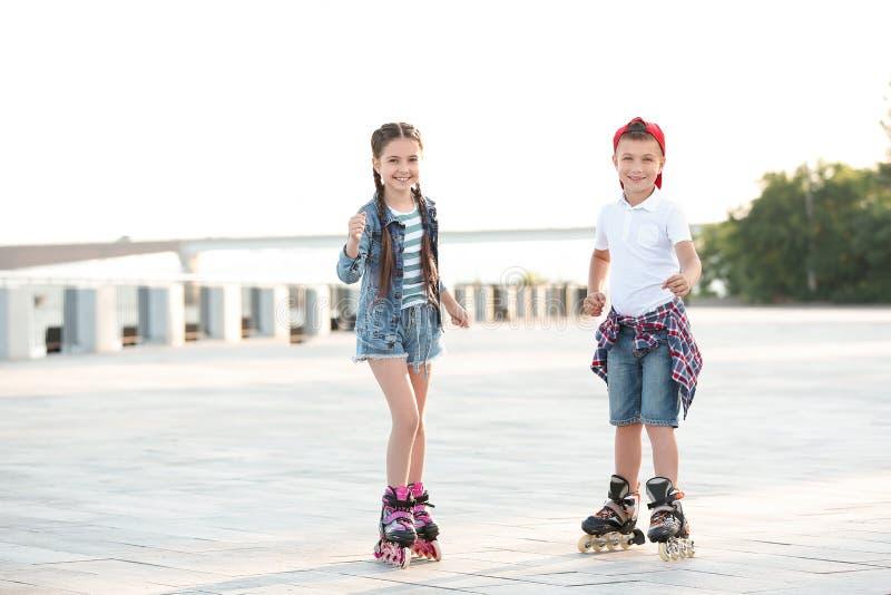 Μικρός κύλινδρος παιδιών που κάνει πατινάζ στην οδό στοκ εικόνα