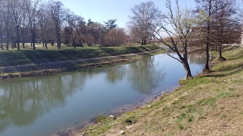 Μικρός ποταμός και η κοίτη του ποταμού μέσω του χωριού με τα δέντρα γύρω από τον ποταμό στοκ εικόνες