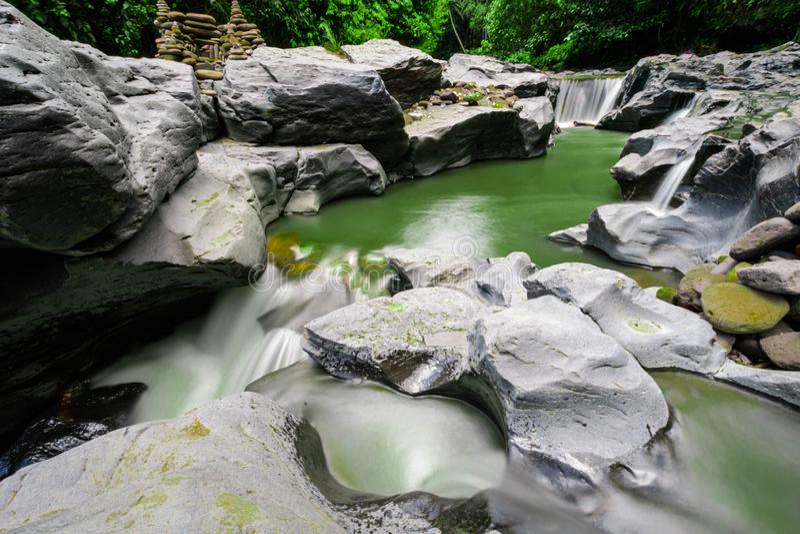 Μικρός ποταμός στο τροπικό δάσος του Μπαλί, μακροχρόνια έκθεση, πράσινο νερό στοκ φωτογραφία