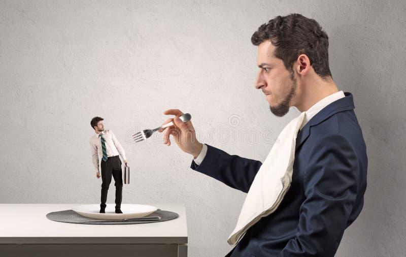 Μικρός φοβησμένος επιχειρηματίας που καταβροχθίζεται σχεδόν στοκ φωτογραφία με δικαίωμα ελεύθερης χρήσης