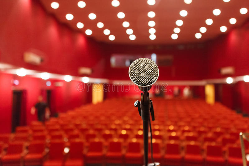 Μικρόφωνο σε ένα υπόβαθρο της κόκκινης αίθουσας με τη διάταξη θέσεων για τους θεατές στοκ εικόνα