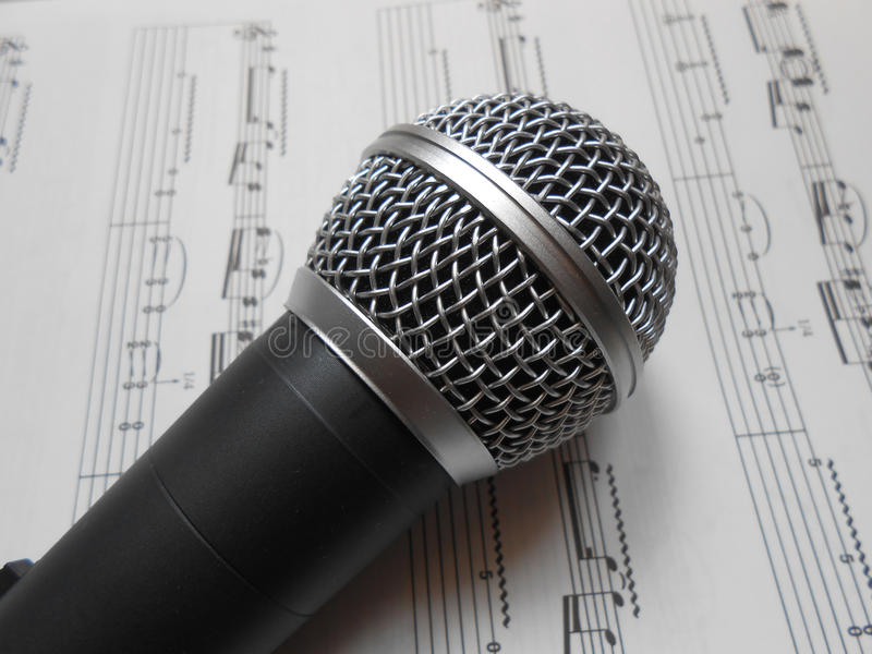 Μικρόφωνο στις σημειώσεις μουσικής στοκ φωτογραφία
