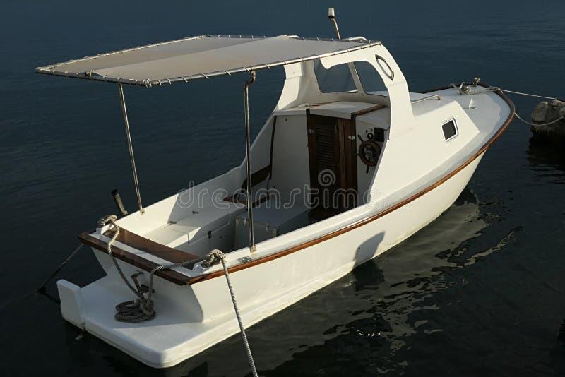 Μικρό άσπρο αλιευτικό σκάφος μηχανών με το ξύλινο τιμόνι, απλή μικρή καμπίνα στο μέτωπο στοκ φωτογραφία με δικαίωμα ελεύθερης χρήσης