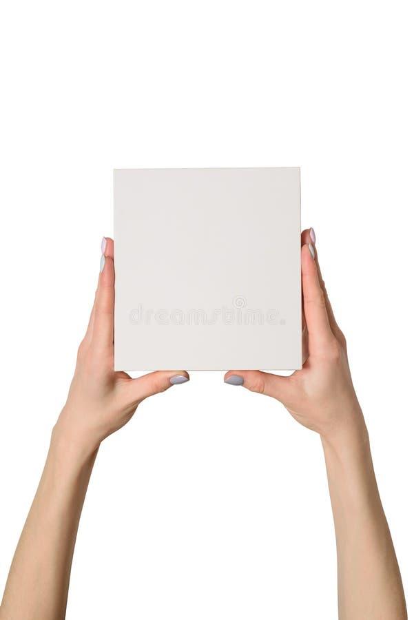 Μικρό άσπρο κουτί από χαρτόνι στα θηλυκά χέρια Τοπ όψη απομονώστε στοκ φωτογραφία