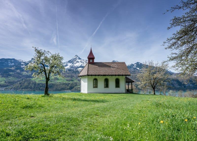 Μικρό άσπρο παρεκκλησι σε ένα θαυμάσιο τοπίο βουνών κατά τη διάρκεια της άνοιξη με μια τυρκουάζ λίμνη πίσω στοκ εικόνες