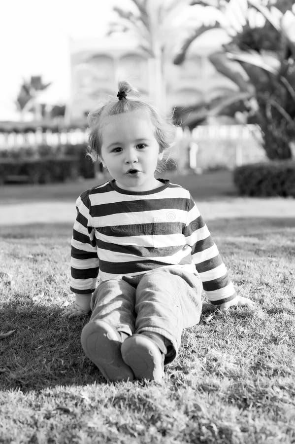 Μικρό αγοράκι με το ευτυχές πρόσωπο στην πράσινη χλόη χωρίς παπούτσια στοκ εικόνες