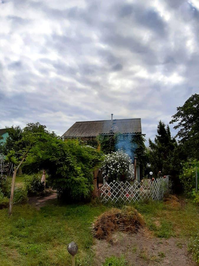 Μικρό αγροτικό σπίτι ενάντια σε έναν θυελλώδη ουρανό, που περιβάλλεται από τα πράσινα φυτά και τους ανθίζοντας Μπους στοκ φωτογραφίες
