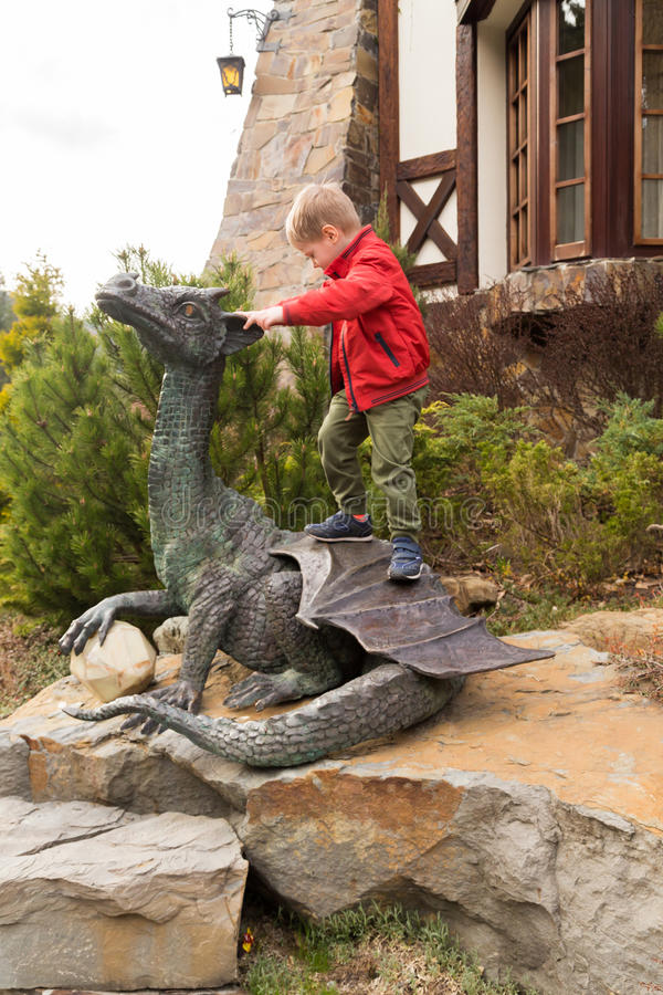 Μικρό αγόρι κοντά σε ένα γλυπτό πετρών ενός δράκου στοκ εικόνα με δικαίωμα ελεύθερης χρήσης
