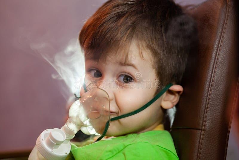 Μικρό αγόρι με μάσκα, θεραπεύει την αναπνευστική οδό με εκνεφωτή στο σπίτι στοκ φωτογραφίες με δικαίωμα ελεύθερης χρήσης