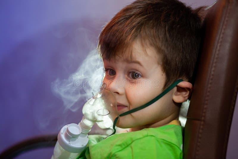 Μικρό αγόρι με μάσκα, θεραπεύει την αναπνευστική οδό με εκνεφωτή στο σπίτι στοκ εικόνες