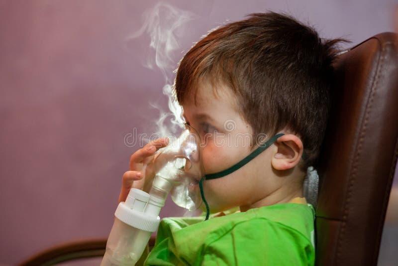 Μικρό αγόρι με μάσκα, θεραπεύει την αναπνευστική οδό με εκνεφωτή στο σπίτι στοκ εικόνα με δικαίωμα ελεύθερης χρήσης