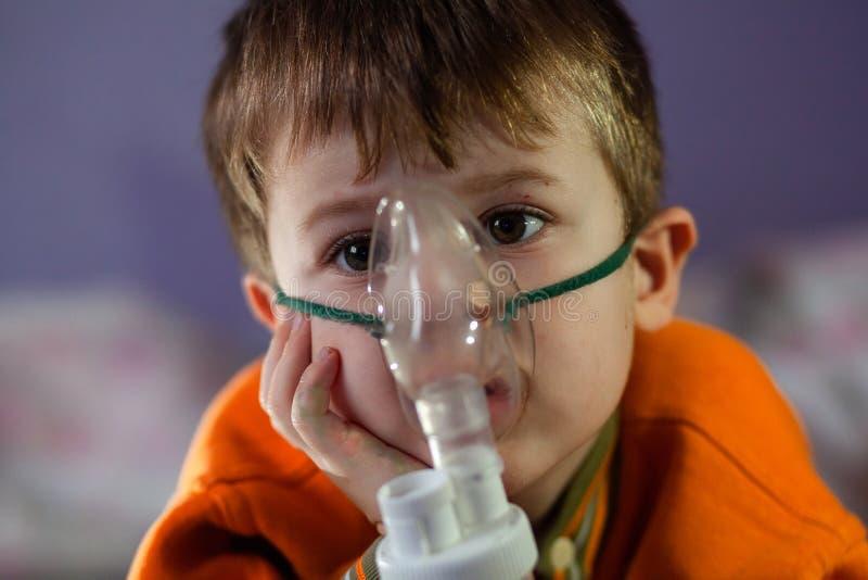Μικρό αγόρι με μάσκα, θεραπεύει την αναπνευστική οδό με εκνεφωτή στο σπίτι στοκ εικόνα