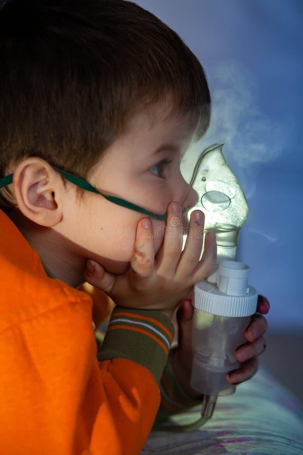 Μικρό αγόρι με μάσκα, θεραπεύει την αναπνευστική οδό με εκνεφωτή στο σπίτι στοκ φωτογραφία με δικαίωμα ελεύθερης χρήσης