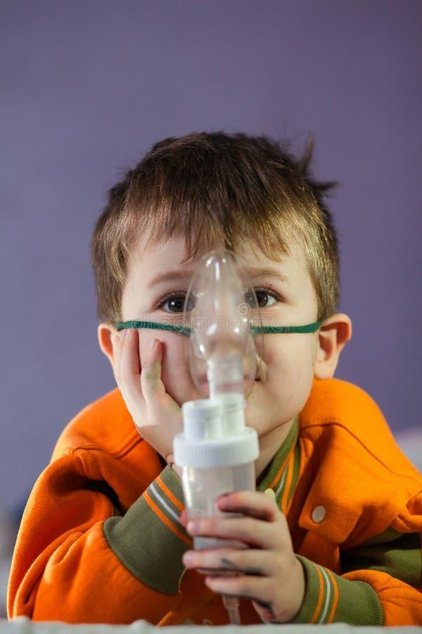 Μικρό αγόρι με μάσκα, θεραπεύει την αναπνευστική οδό με εκνεφωτή στο σπίτι στοκ φωτογραφία
